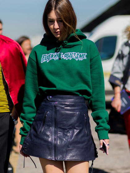 A woman attending fashion week wearing a hoodie and a leather skirt.