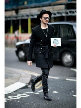 Ein junger Mann in London kombiniert seine schwarzen Lederstiefel mit passender Hose aus Glattleder.