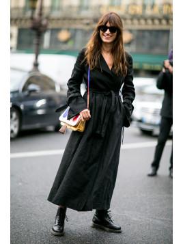 Eine junge Frau trägt einen knöchellangen Mantel mit punkigen Schnürstiefeln und bunter Handtasche.