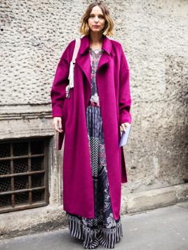 Das Model Candela Novembre erscheint in einem gemusterten Maxikleid mit Umhängetasche und leuchtendem Mantel im Oversize-Look.