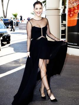 Barbara Palvin trägt ein schwarzes Maxikleid im rockigen Look. Klassische spitze Pumps runden ihr Outfit ab.
