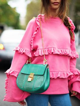 Sara Lava trägt eine grüne kleine Handtasche zu einem knalligen pinkfarbenen Shirt.