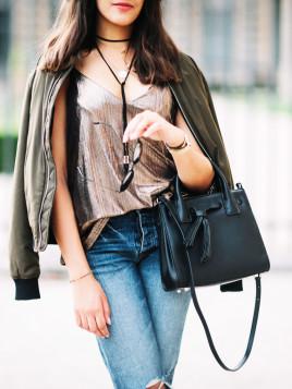 Fashion-Bloggerin Sarah Benziane trägt eine Bomberjacke und dazu eine klassische schwarze Handtasche.