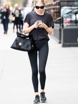 Model Elsa Hosk komplett in schwarz gekleidet mit dunkler Handtasche in der Armbeuge.