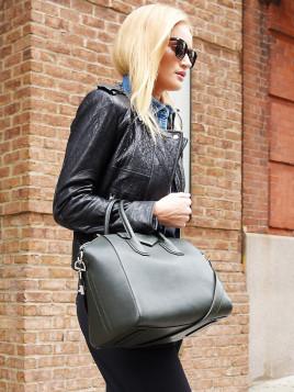 Rosie Huntington-Whiteley trägt eine große schwarze Tasche in der Armbeuge. Dazu kombiniert sie eine schwarze Lederjacke.