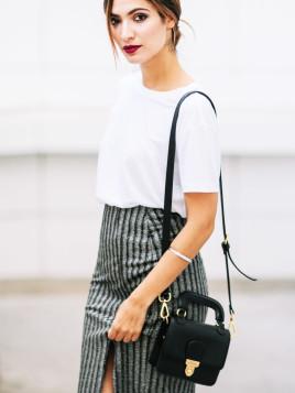 Fashion-Bloggerin Sofya Benzakour trägt eine schwarze kleine Tasche und dazu einen gestreiften Rock.