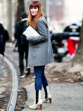 Diese Frau kombiniert weiße Lederstiefel mit XXL-Mantel.