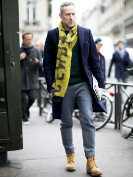 Pariser Mann kombiniert Timberland-Stiefel mit blauem Mantel und gelbem Schal.