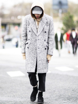 Junger Mann in Paris trägt wildlederne Stiefel zu beigem Kapuzenpullover und Cap.