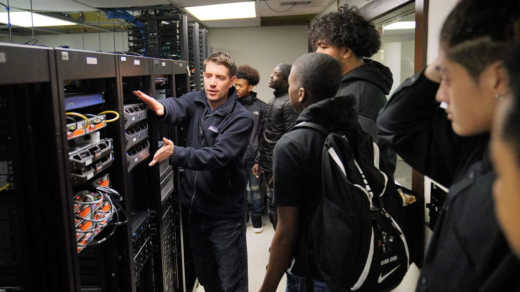 an information technology manager teaching students in front of a computer server
