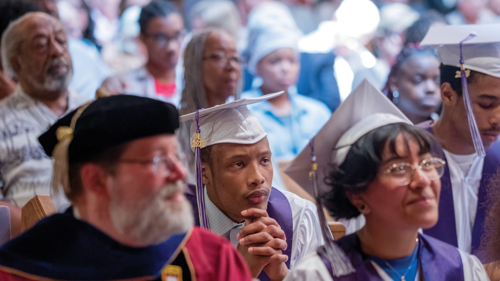 graduates and a professor listen to a speaker at a high school graduation