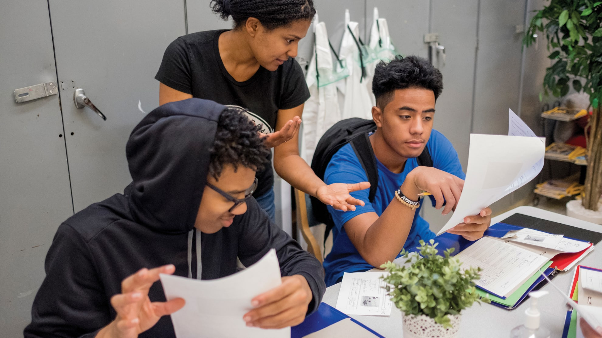 A teacher explaining an assignment to two high school students sitting at a table.