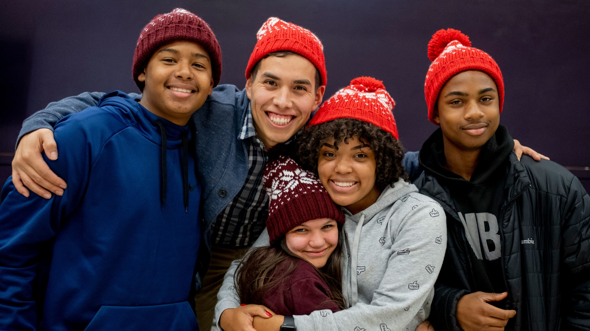 a teacher and students wearing hats and smiling for a picture