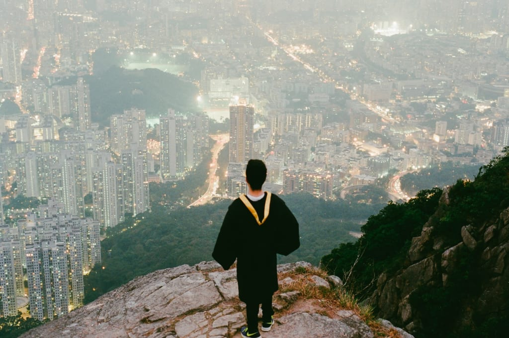 person in black top standing on cliff over looking buildings
