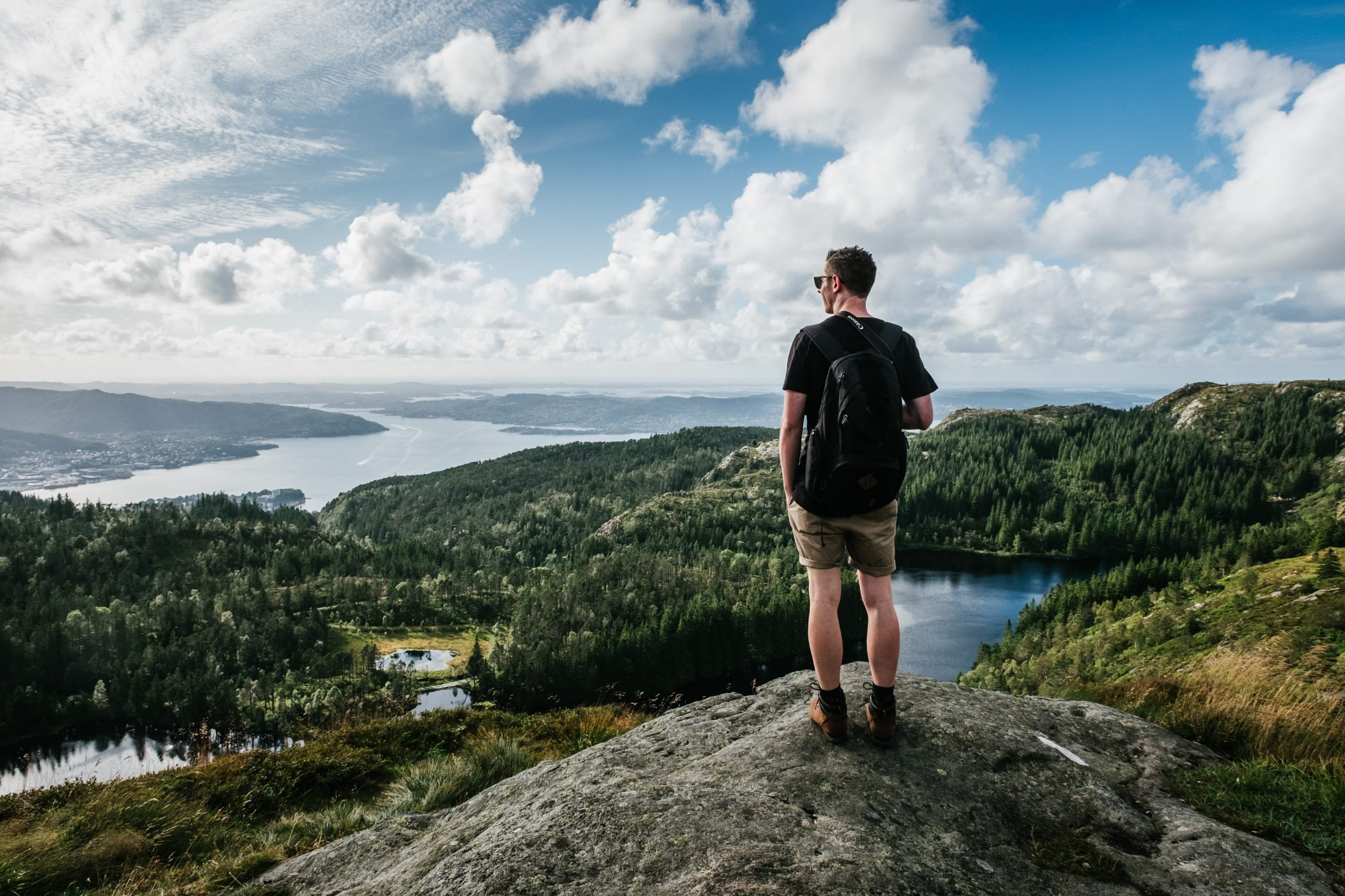 Young man standing on a rock overlooking a breathtaking view of trees and cloudy skies