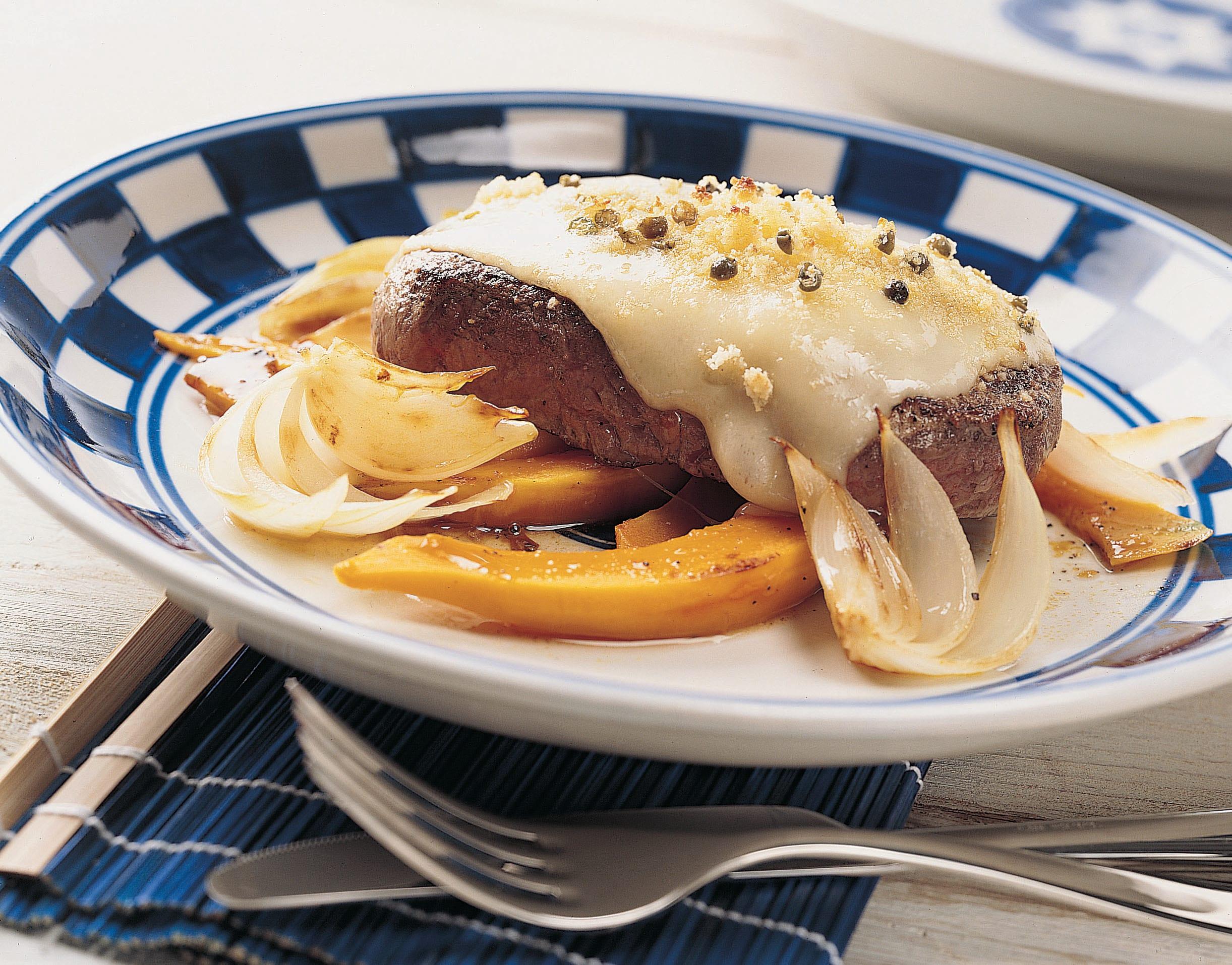 Entrecôtes au fromage et au poivre sur lit d'oignons et de courge