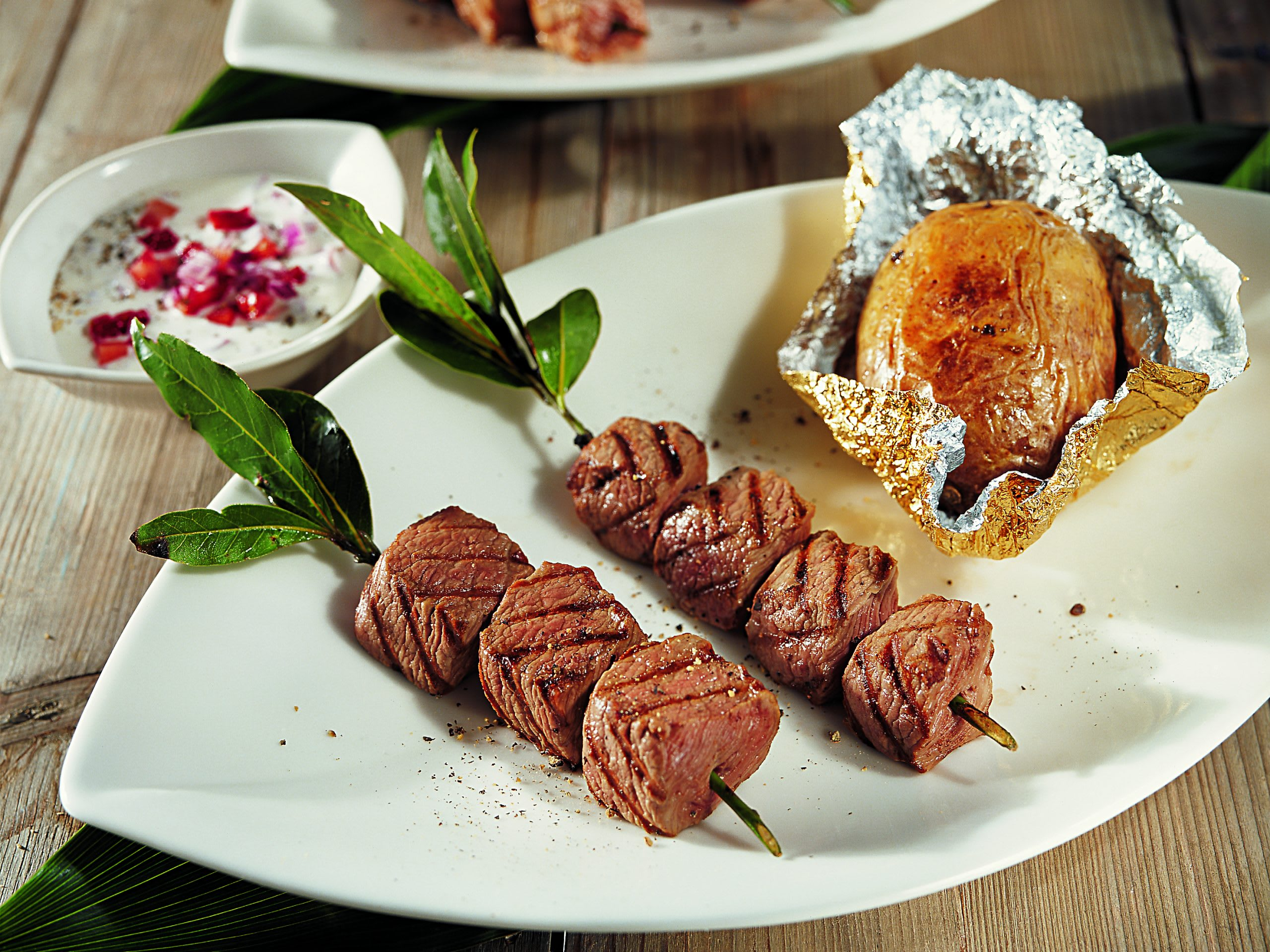 Brochettes d'agneau au barbecue, baked potatoes et sauce