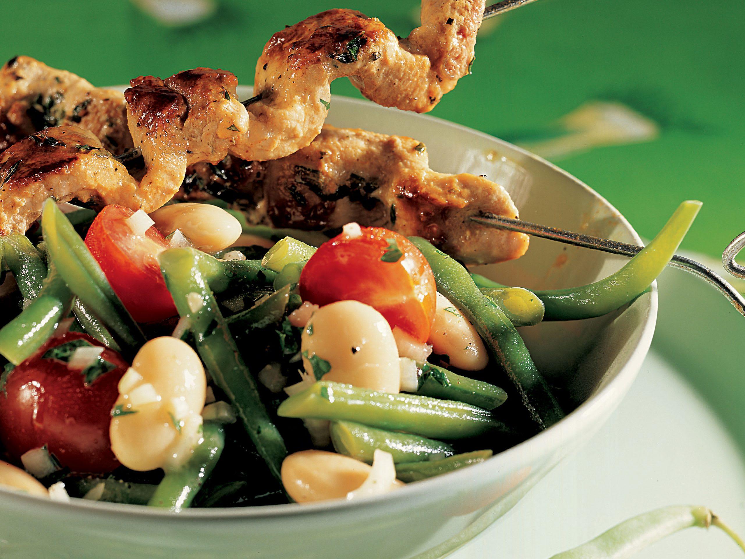 Brochettes de porc sur lit de salade de haricots
