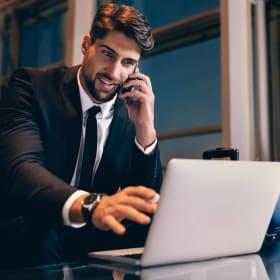 Homme en costume étant au téléphone et utilisant son PC portable