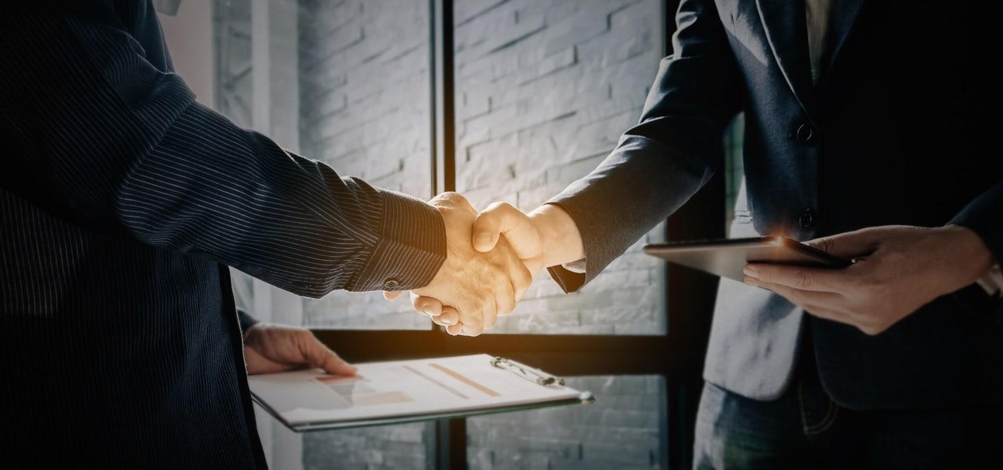 Personnes en costume se serrant la main