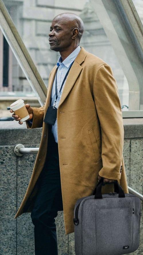Personne marchant dans la rue avec son café et sa sacoche