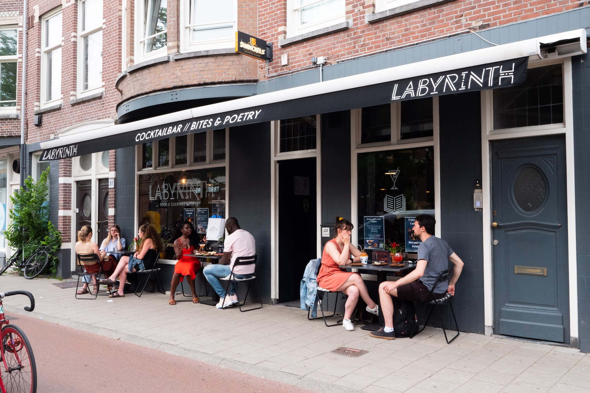 Happy diners sitting outside one of Amsterdam's best restaurants and cocktail bars- Labyrinth