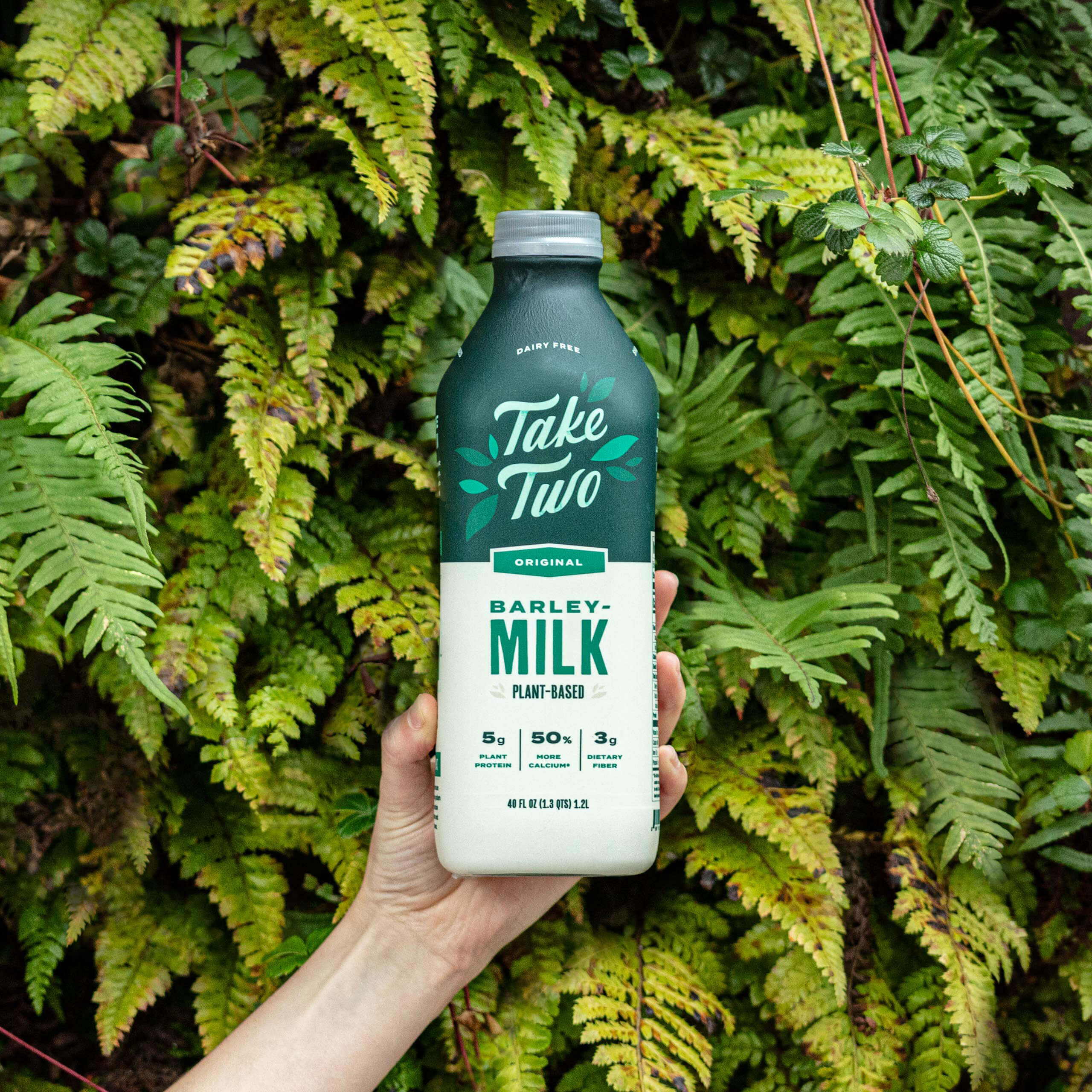 Hand holding a Take Two Barleymilk bottle against plant backdrop