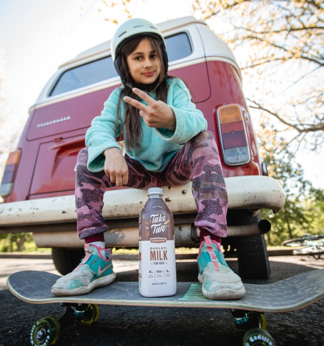 Girl on skateboard with bottle of Take Two.