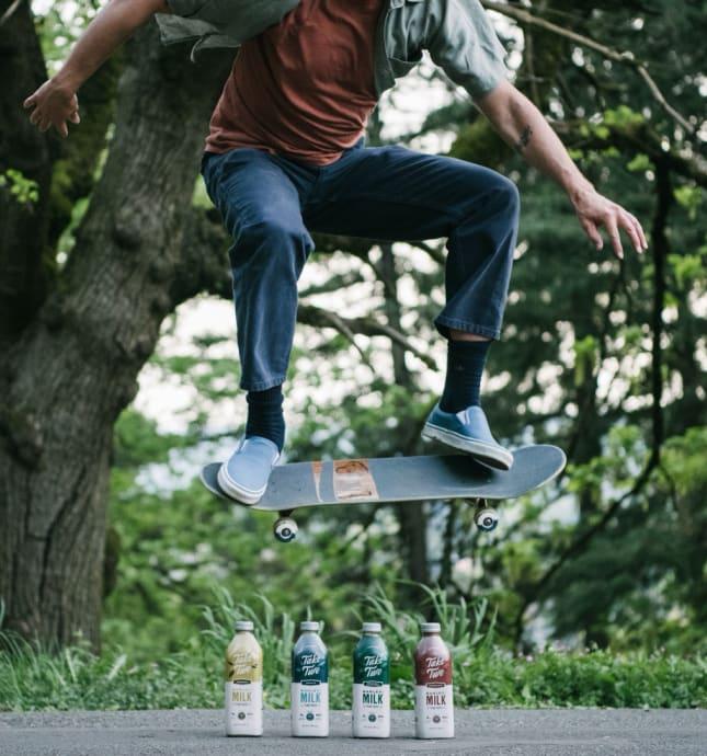 Guy on skateboard over bottles of Take Two Barleymilk.