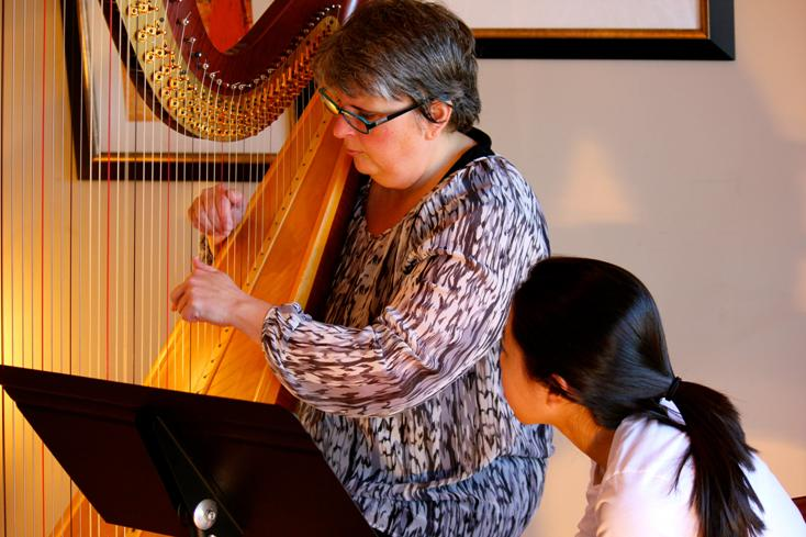 Harp Teacher Tisha demonstrates a harp technique for Lauren