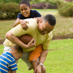kids and dad playing football