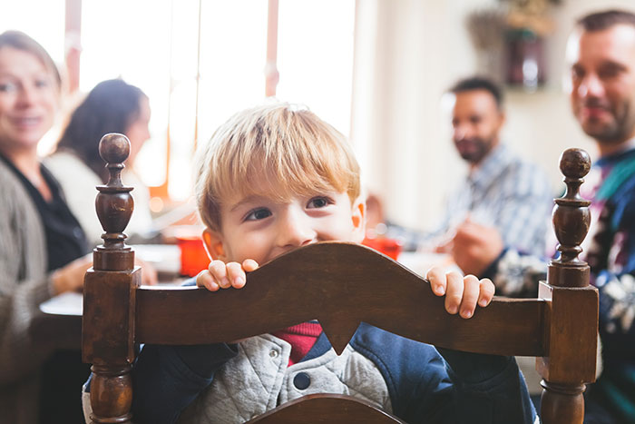 Boy peeking over chair to symbolize family activities that keep the spirit of Christmas alive