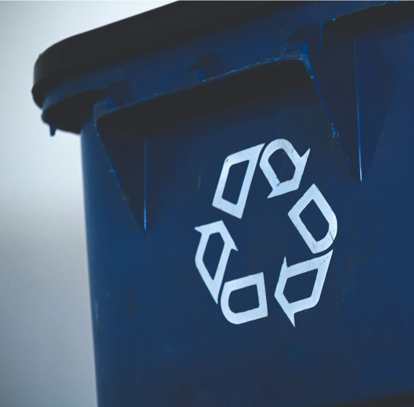 A close-up view of a blue recycling bin with a white recycling symbol of three arrows forming a triangle