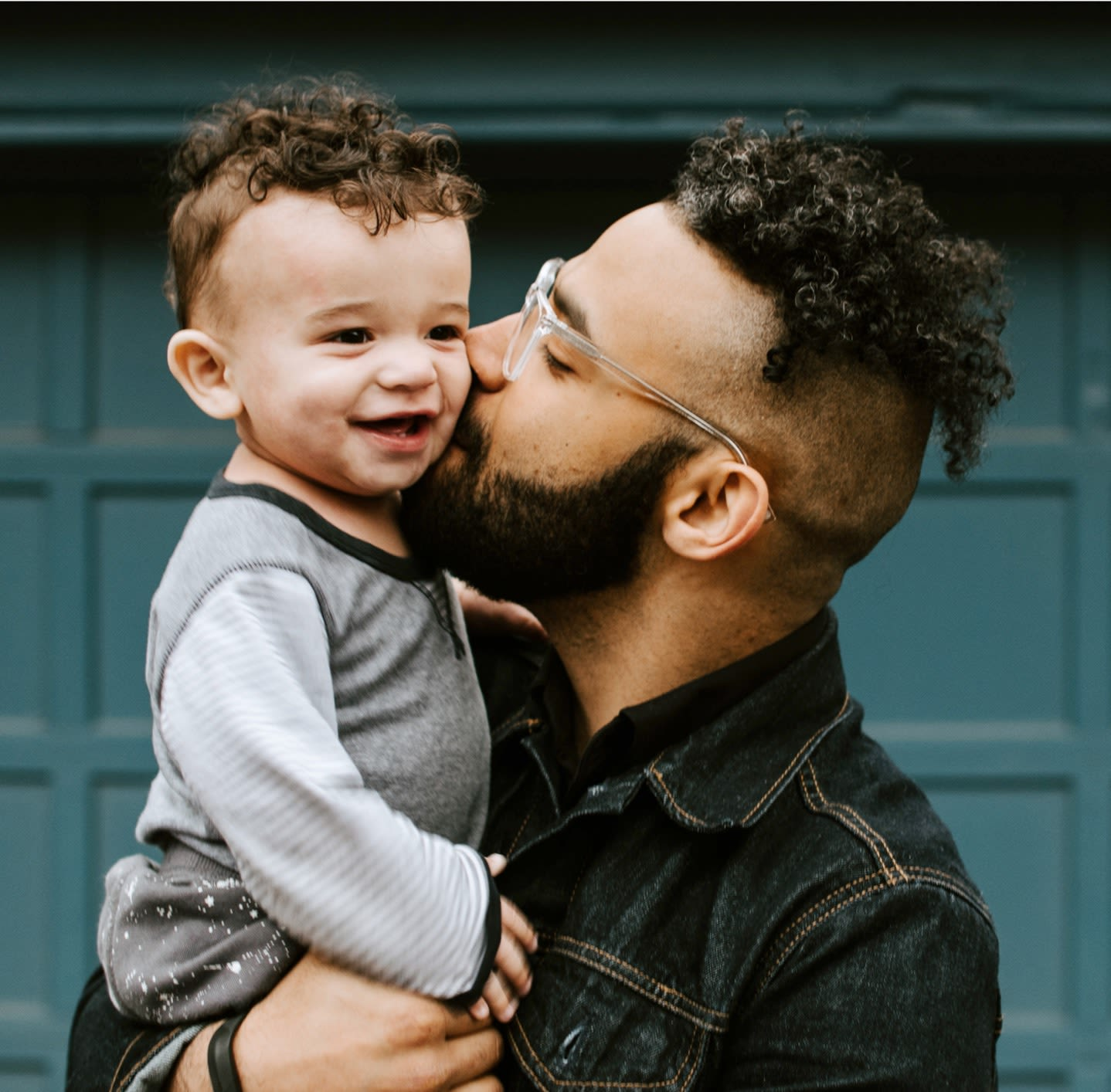 Man with curly hair and glasses holding a toddler boy with curly hair in his arms and kissing him on the cheek