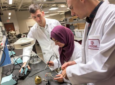 Three Engineering Medicine students working on electrical equipment