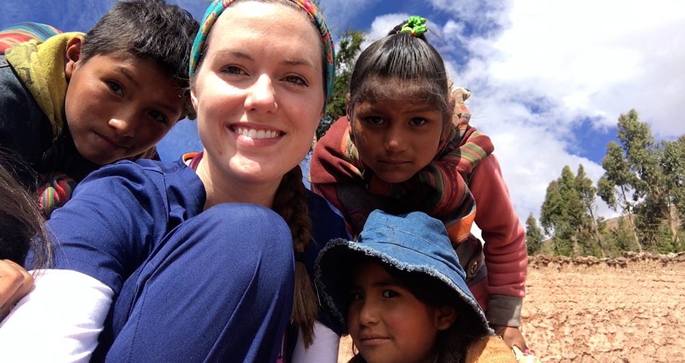 Student Hanna Himes posing with children during a mission trip to Bolivia