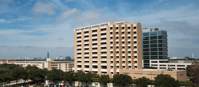 Houston campus building with Houston skyline in the background