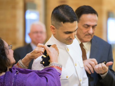 A medical student receiving his miliary commission. His parents putting his epaulettes on his uniform
