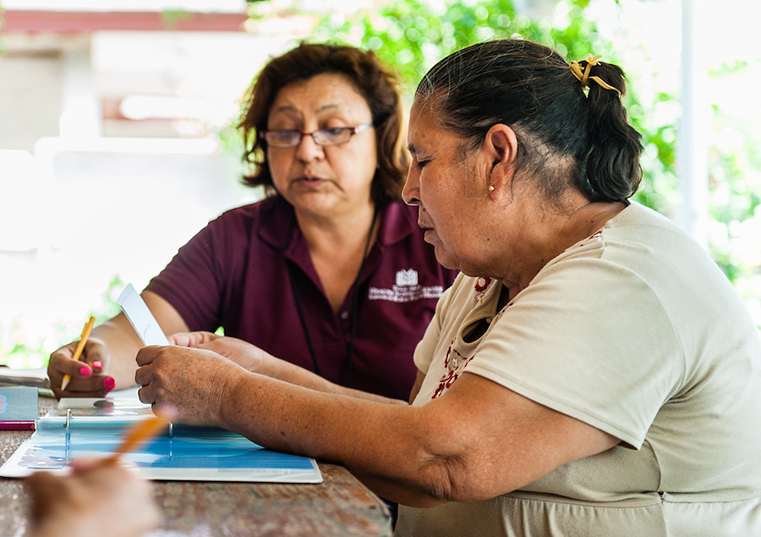 Health care worker reviewing literature with a patient at her rural home