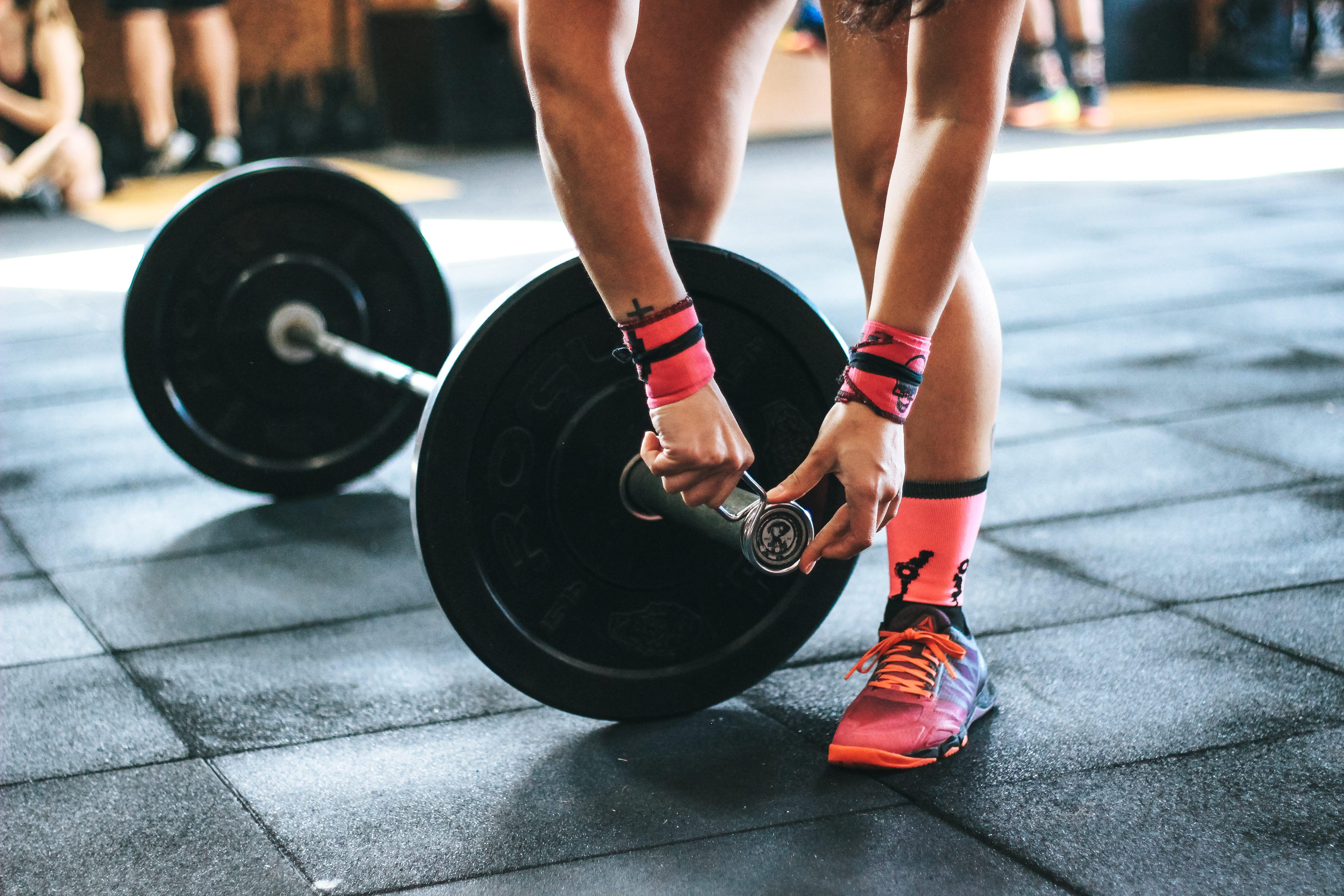 Eine Frau fixiert eine Gewichtsscheibe auf der Langhantel
