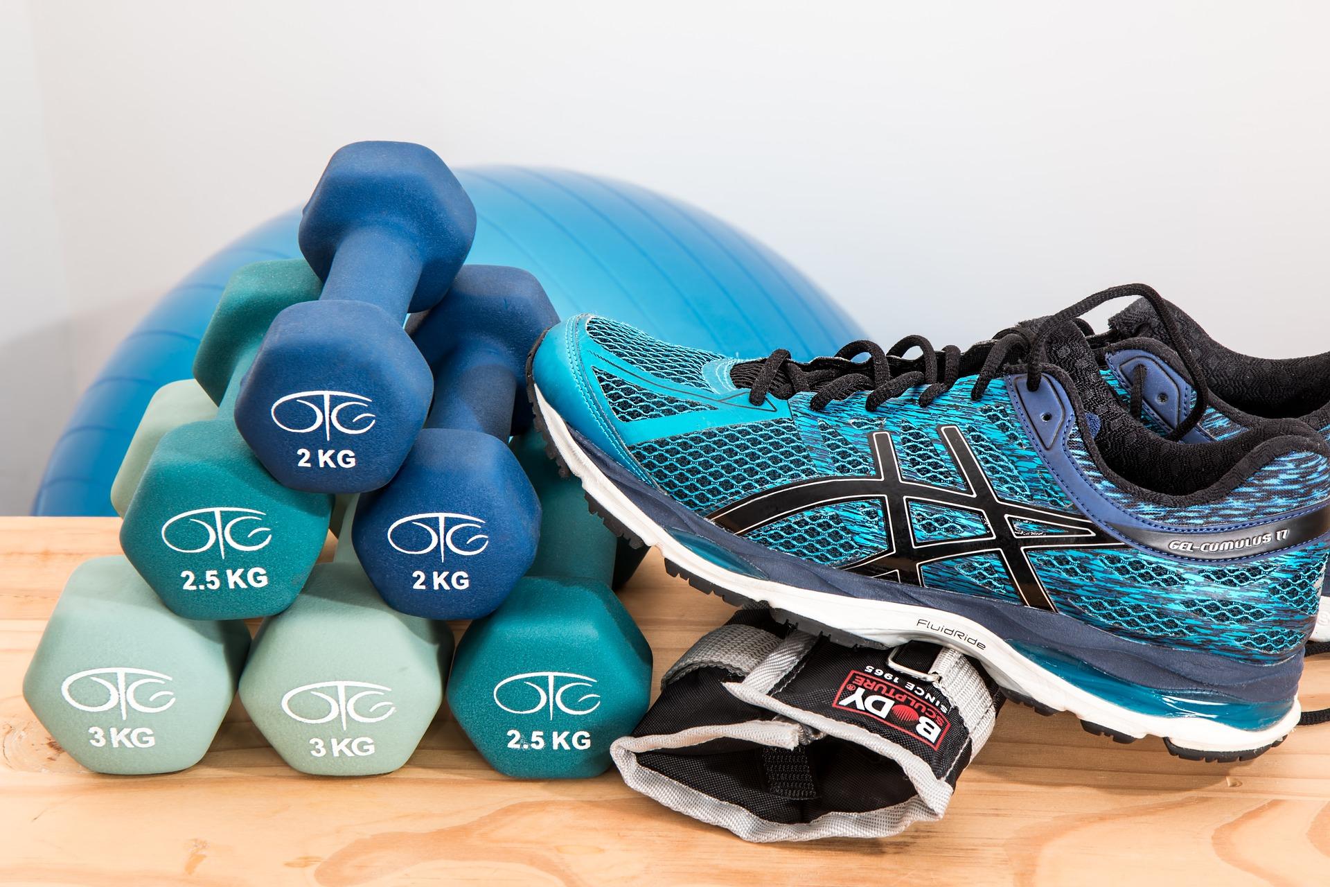 Hanteln, ein Laufschuh und ein Gymnastikball.