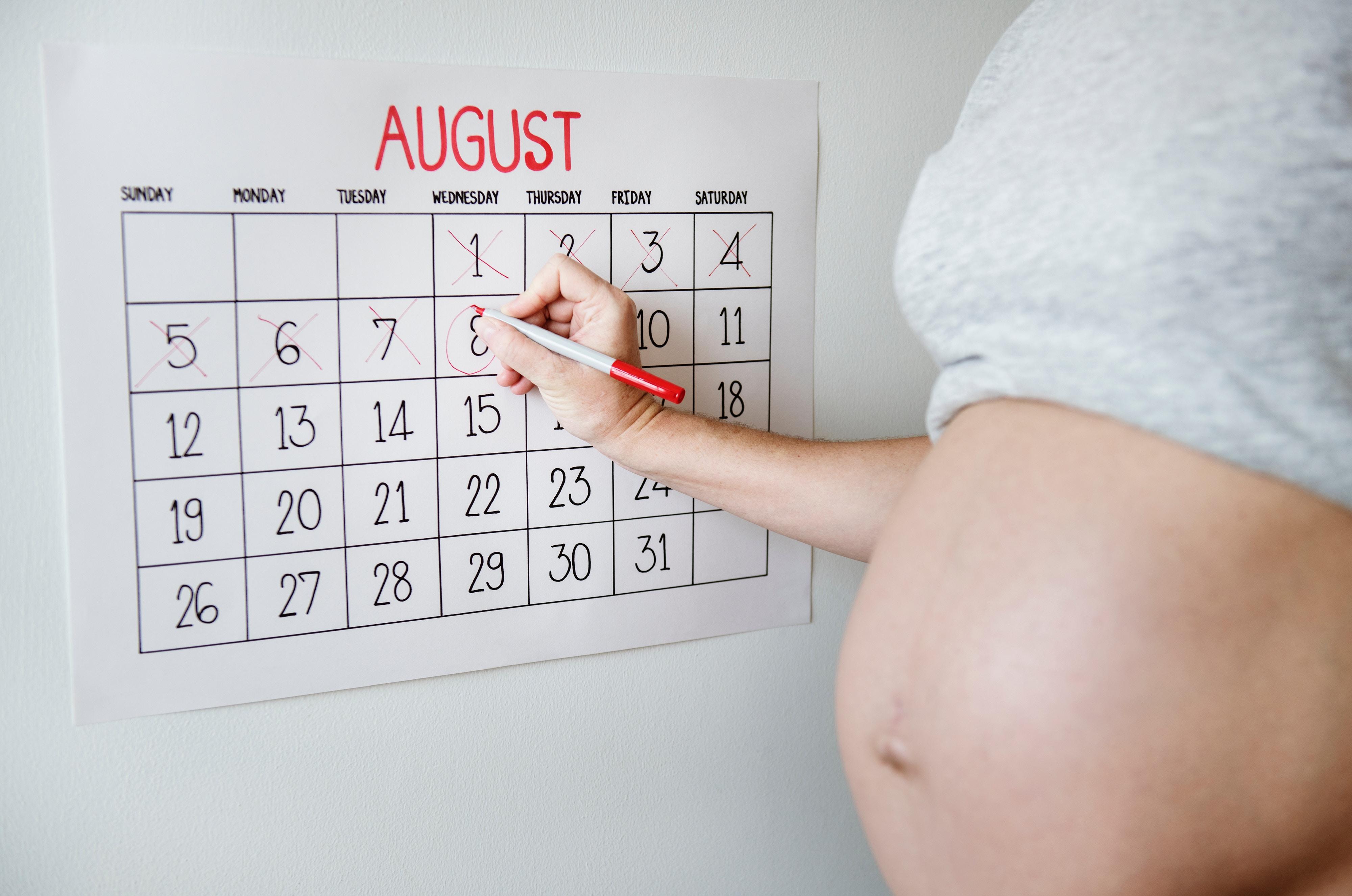Schwangere Frau, die auf einem Kalender die Tage bis zur Geburt ankreuzt.
