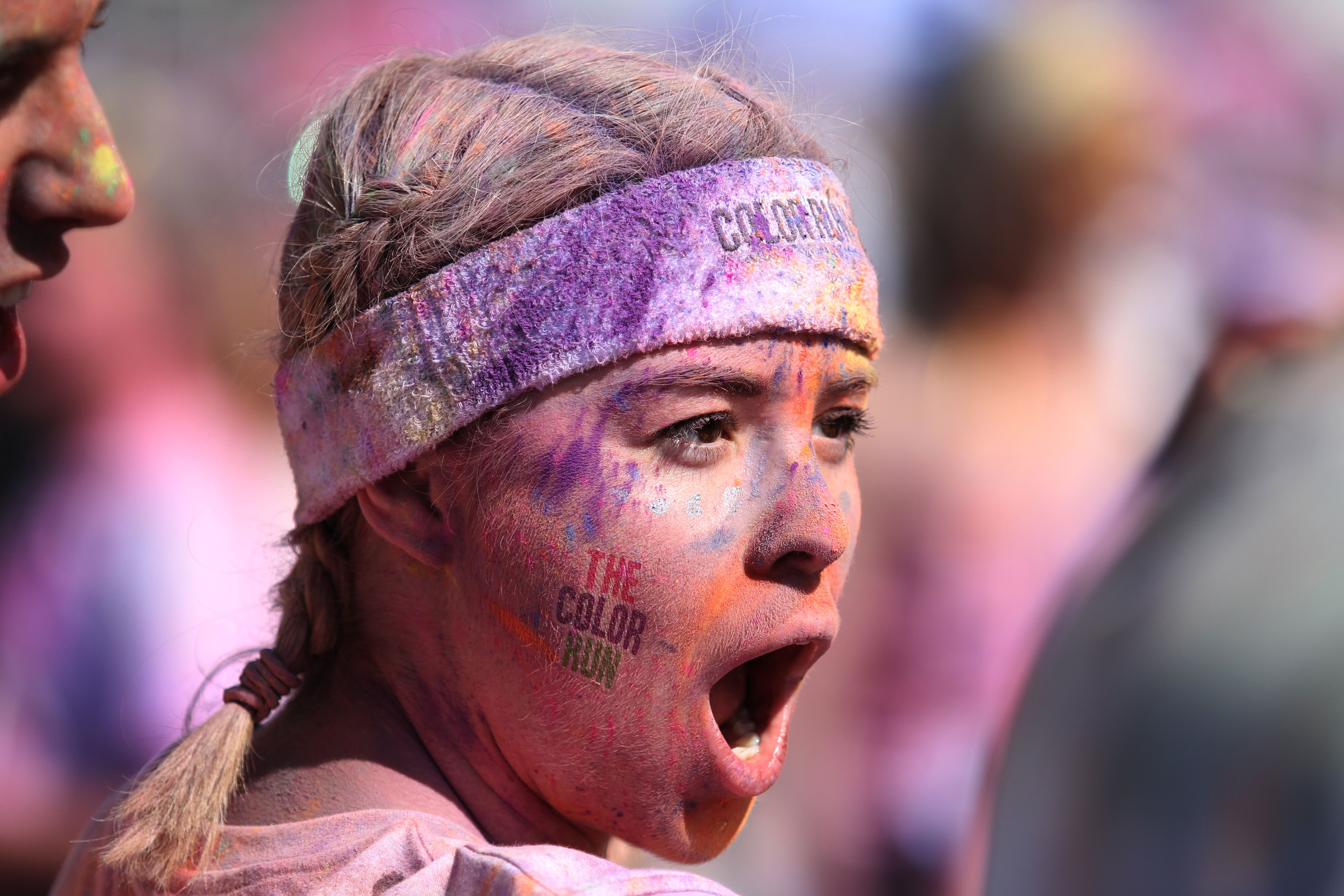 Gesicht voller Farbe von einer Frau am The Color Run