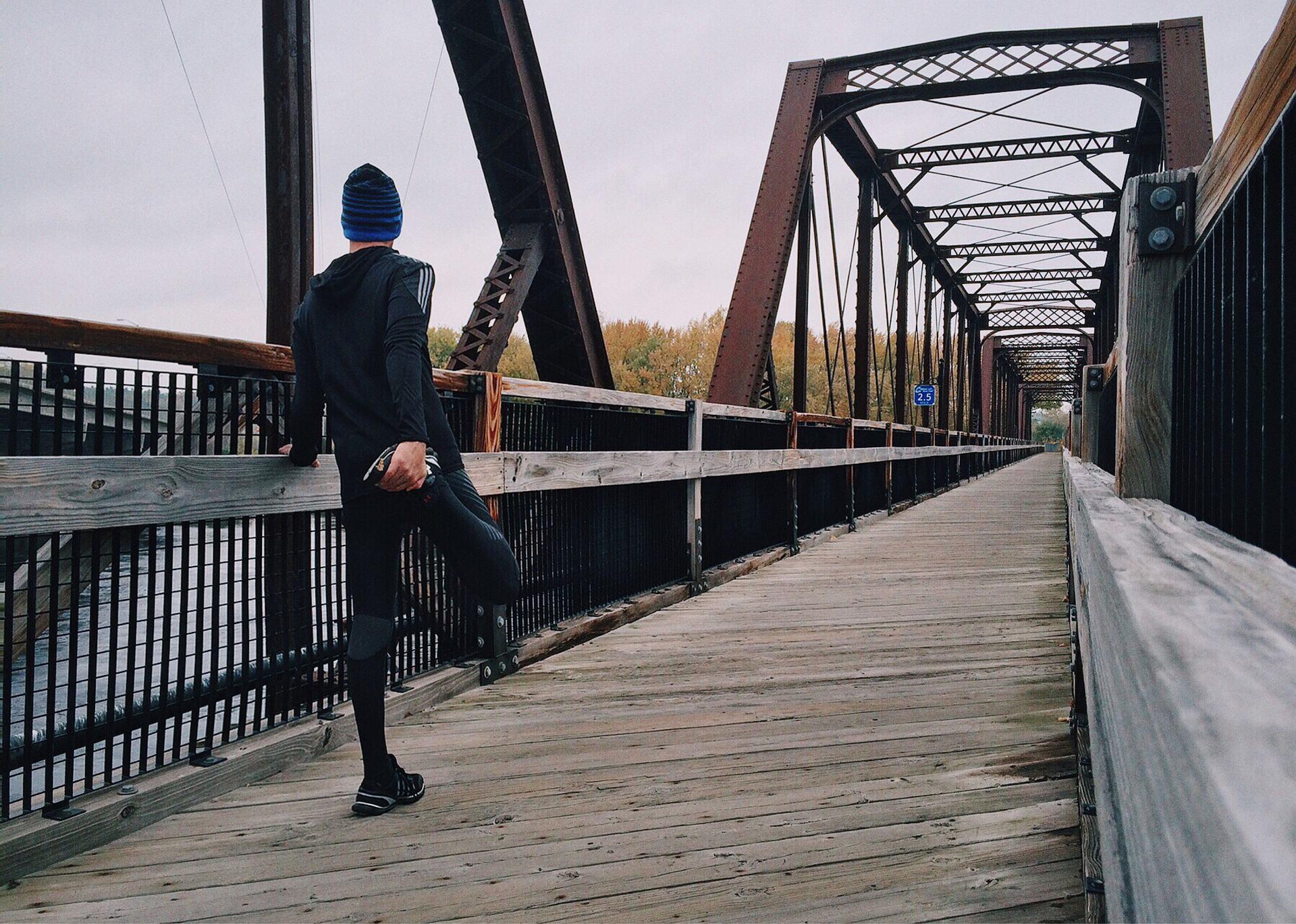 Ein Mann dehnt die Waden auf einer Brücke