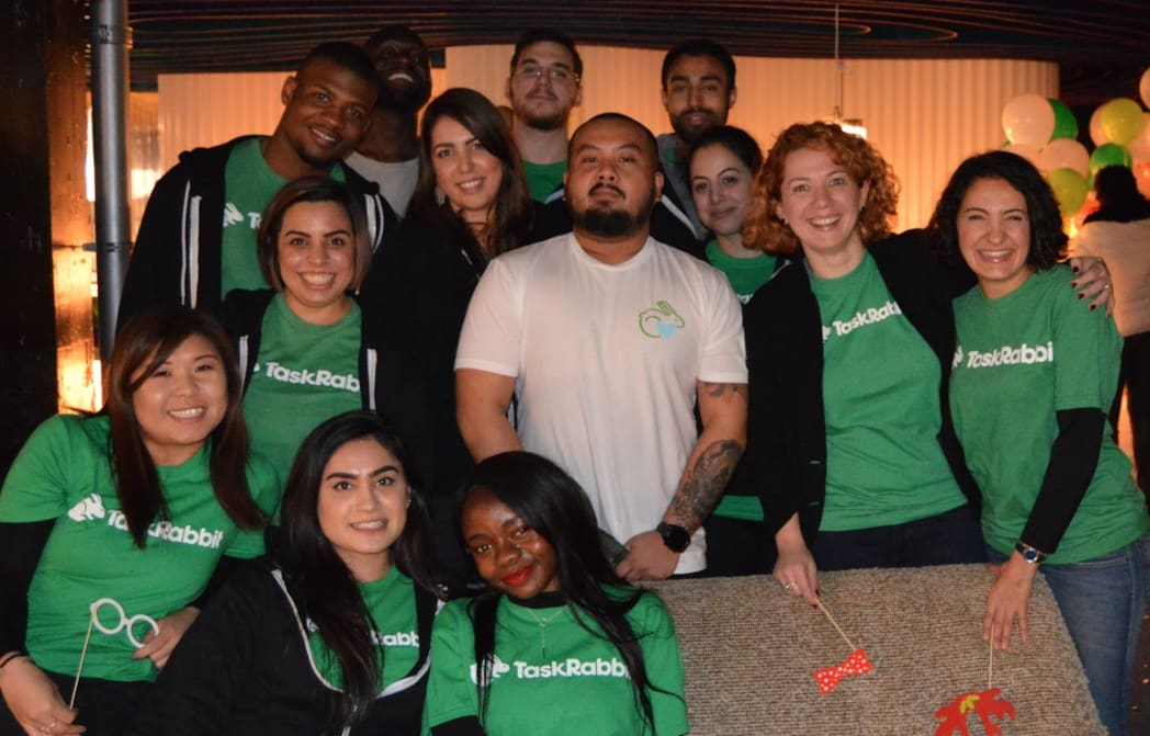 Smiling employees wearing green and white TaskRabbit logo t-shirts pose for a picture.