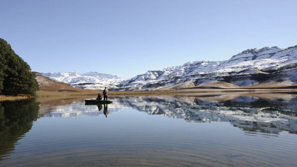 Drakensberg flyfishing for trout against a backdrop of snow at giants cup wilderness reserve sezyfa