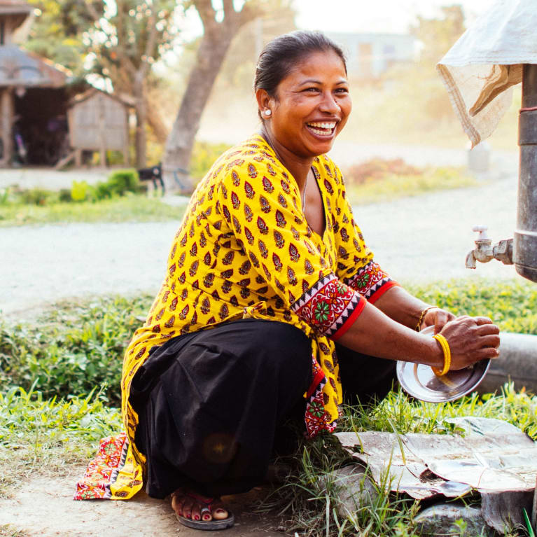 Alina washes plates outside her store in Nepal. Photo: Tom Price/Tearfund