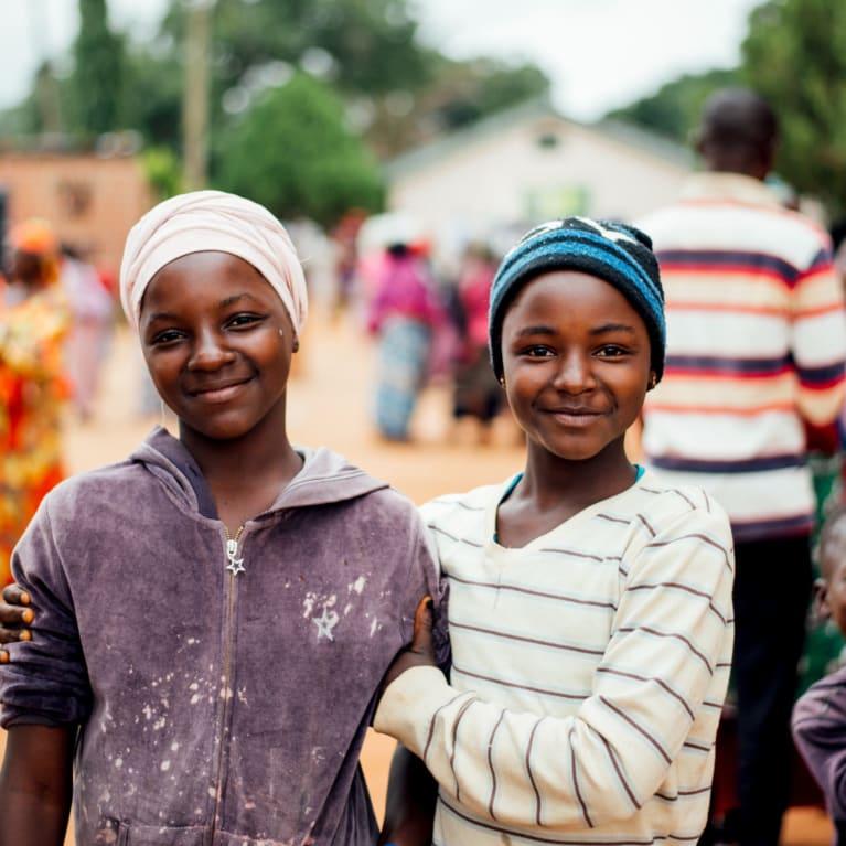 Two girls stand shoulder to shoulder at a refugee camp in Nigeria
