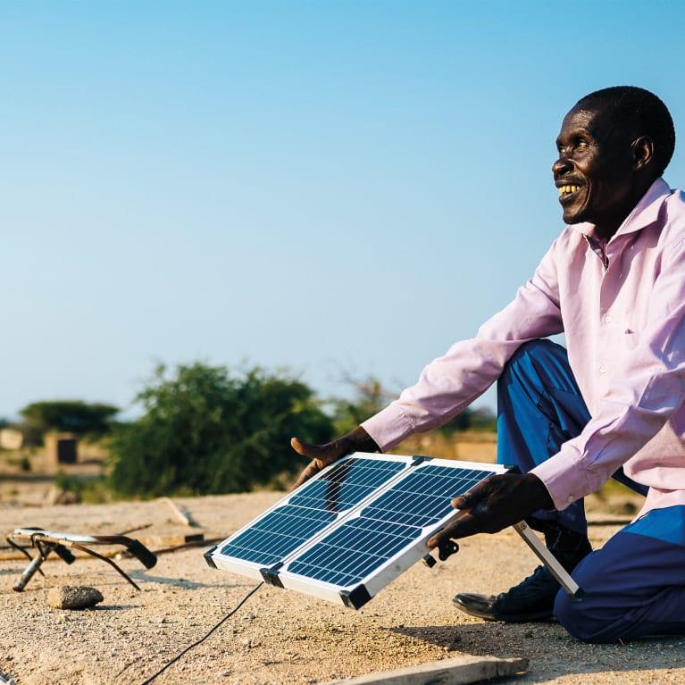 En Tanzanie, Lameck Chibago prend soin du panneau solaire installé sur le toit de sa maison. Photo : Tom Price – Ecce Opus/Tearfund