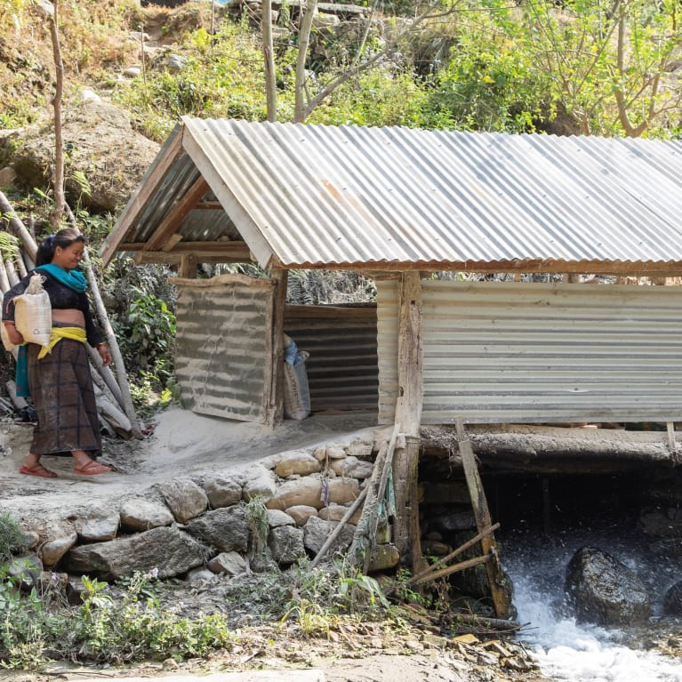 Phul Kumari brings grain to a mill powered by water flowing from the micro-hydropower plant above.